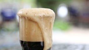 Een volledig glas schuimend donker bier stock footage