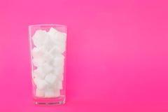 Een volledig transparant glas van suikerkubussen op een heldere roze achtergrond Witte stukken kubussenrisico's met betrekking to Stock Foto
