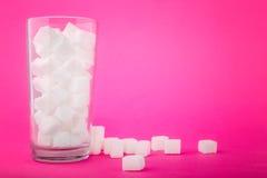 Een volledig transparant glas van suikerkubussen op een heldere roze achtergrond Witte stukken kubussenrisico's met betrekking to Stock Foto's