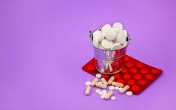 Een volledige emmer van ronde tabletten en een rode verpakking van pillen op l Royalty-vrije Stock Fotografie