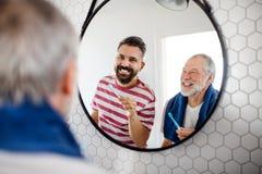 Een volwassen hipsterzoon en een hogere vader in badkamers die binnen thuis, tanden borstelen stock afbeelding