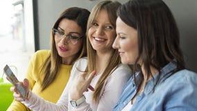 Een volwassen meisje toont haar vrienden een foto van haar nieuwe vriend stock foto