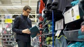 Een volwassen mens bekijkt een thermisch jasje, controleert hij de kwaliteit van het aan de aanraking stock footage