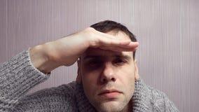 Een volwassen mens die in de afstand turen De man verheugt zich op met zijn hand zijn hoofd stock videobeelden