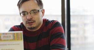 Een volwassen mens in glazen spreekt in een koffie stock videobeelden