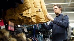 Een volwassen mens kiest een de winterjasje, zijn de kleren op een rek in een winkelcentrum stock videobeelden