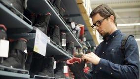 Een volwassen mens kiest de winterlaarzen, die op de teller van een winkelcentrum zijn stock video