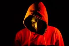 Een volwassen mens kijkt uit van onder de kap met een grijns zoals psycho of een maniak in een oranje sweatshirt met een kap dat  royalty-vrije stock foto's