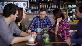 Een volwassen mens met kort haar, gekleed in een plaidoverhemd, vertelt zijn vrienden dat met hem bij een houten lijst over laats stock footage