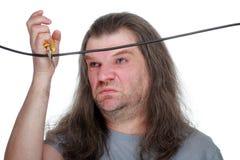 Een volwassen mens met lange haarsnacks de draad met draadscharen, g Royalty-vrije Stock Fotografie