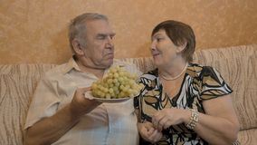 Een volwassen paar eet druiven, en voer elkaar Close-up stock footage