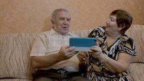 Een volwassen paar gebruikt een tablet, zitten zij op de laag stock videobeelden