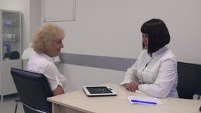 Een volwassen paar is geinteresseerd in een gehoorapparaat stock videobeelden