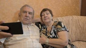 Een volwassen paar maakt selfie Gebruik een smartphone voor foto's stock video