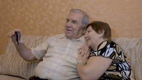 Een volwassen paar maakt selfie Gebruik een smartphone voor foto'sclose-up stock footage