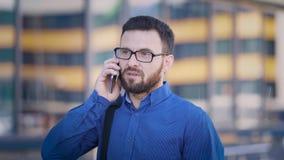 Een volwassen specialist van een groot bedrijf spreekt op een mobiele telefoon, bevindt een mens zich buiten in een WiFi-streek,  stock footage