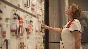 Een volwassen vrouw bekijkt pennen voor meubilair, kiest zij toebehoren voor de deur stock footage