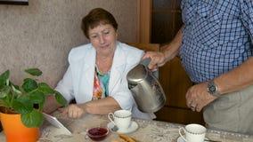 Een volwassen vrouw die een tablet gebruiken, drinkend thee bij de lijst stock video