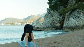Een volwassen vrouw voert yogaoefeningen op kust bij klippen uit stock video