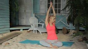 Een volwassen vrouw zit op het zand en doet een opwarming van handen stock videobeelden
