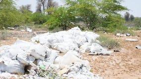 Een voorbeeld van plastiek en ander die draagstoel of huisvuil in de woestijn wordt geworpen die potenti?le milieuzorgen veroorza stock video