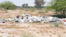 Een voorbeeld van plastiek en ander die draagstoel of huisvuil in de woestijn wordt geworpen die potenti?le milieuzorgen veroorza stock videobeelden