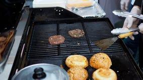 Een voorbereiding van hamburgerrundvlees het barbecuing op een heet gasfornuis stock afbeeldingen