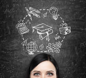 Een voorhoofd van de dame die over het bestuderen en graduatie denkt De onderwijspictogrammen worden getrokken op het zwarte bord Royalty-vrije Stock Afbeelding