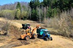 Een voorlader laadt afval in een tractor wanneer het aanleggen van een weg op een bebost gebied stock foto's