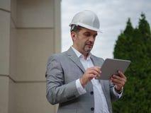 Een voorman met tablet op een industriële achtergrond Bouwer die elektronika gebruiken Bouwtechnologieconcept De ruimte van het e royalty-vrije stock foto's