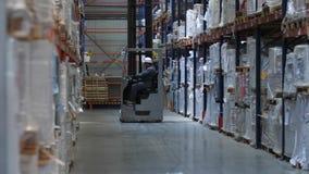 Een vorkheftruck drijft langs reusachtige tribunes met goederen in een logistisch pakhuis 4K langzame mo stock footage