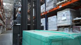 Een vorkheftruck met een doos berijdt langs de tribunes bij het pakhuis 4K langzame mo stock video