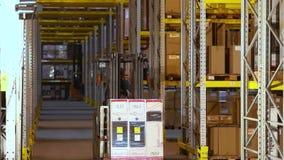 Een vorkheftruck met dozenritten tussen rijen in een pakhuis, een mens drijft een vorkheftruck in een pakhuis Het werk in een pak stock video