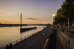 Een vrachtboot die langs de rivier Rijn bij schemer in Dusseldorf, Duitsland reizen stock afbeeldingen