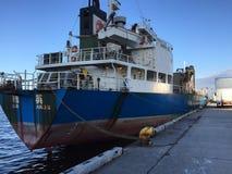 Een vrachtschip legt bij de haven vast stock afbeelding