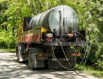 Een vrachtwagen met een reservoir voor het vervoeren van teer of bitumen aan de kant van een weg in een openbaar park Reparatie v stock foto