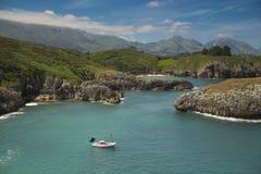 Een vreedzame dag over een boot dicht bij de kust en de berg Stock Foto's