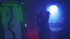 Een vreemd ruimteschip, een vrouw in metaalpantser, met lang dreadlocks bevindt zich en onderzoekt de patrijspoort, 4k stock footage
