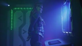 Een vreemde invaller in het ruimteschip bekijkt het scherm op de muur, 4k stock videobeelden