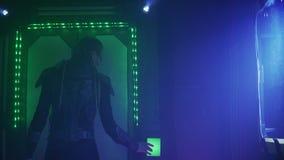 Een vreemdeling in lichaamspantser gebruikt een controlebord op de deur in het ruimteschip, 4k stock video