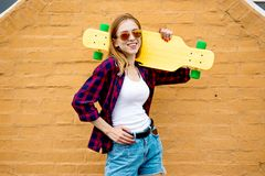 Een vrij blond glimlachend meisje die zonnebril, geruite overhemd en denimborrels dragen bevindt zich voor de bakstenen muur royalty-vrije stock foto