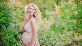 Een vrij zwanger meisje met blond golvend haar dat het fladderen rond, in een helder bos van de de zomerochtend, in leuk windt stock video