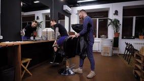 Een vrije en actieve kapper spreekt aan een cliënt van herenkapper, wil een mens te weten komen welk kapsel de cliënt van stock footage