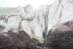 Een vrije klimmer met een ijsbijl in zijn hand bevindt zich binnen bij de voet van de Grote Gletsjer naast een epische barst in d royalty-vrije stock afbeelding