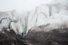 Een vrije klimmer met een ijsbijl in zijn hand bevindt zich binnen bij de voet van de Grote Gletsjer naast een epische barst in d stock foto