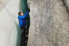 Een vrije klimmer zonder verzekering met ijs twee schaft stijgingen van een barst van de gletsjer af Het vrije beklimmen zonder k royalty-vrije stock afbeelding