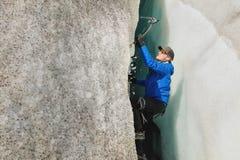 Een vrije klimmer zonder verzekering met ijs twee schaft stijgingen van een barst van de gletsjer af Het vrije beklimmen zonder k royalty-vrije stock foto's