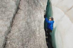 Een vrije klimmer zonder verzekering met ijs twee schaft stijgingen van een barst van de gletsjer af Het vrije beklimmen zonder k stock foto's