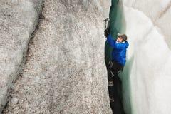 Een vrije klimmer zonder verzekering met ijs twee schaft stijgingen van een barst van de gletsjer af Het vrije beklimmen zonder k royalty-vrije stock afbeeldingen