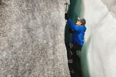 Een vrije klimmer zonder verzekering met ijs twee schaft stijgingen van een barst van de gletsjer af Het vrije beklimmen zonder k stock afbeeldingen